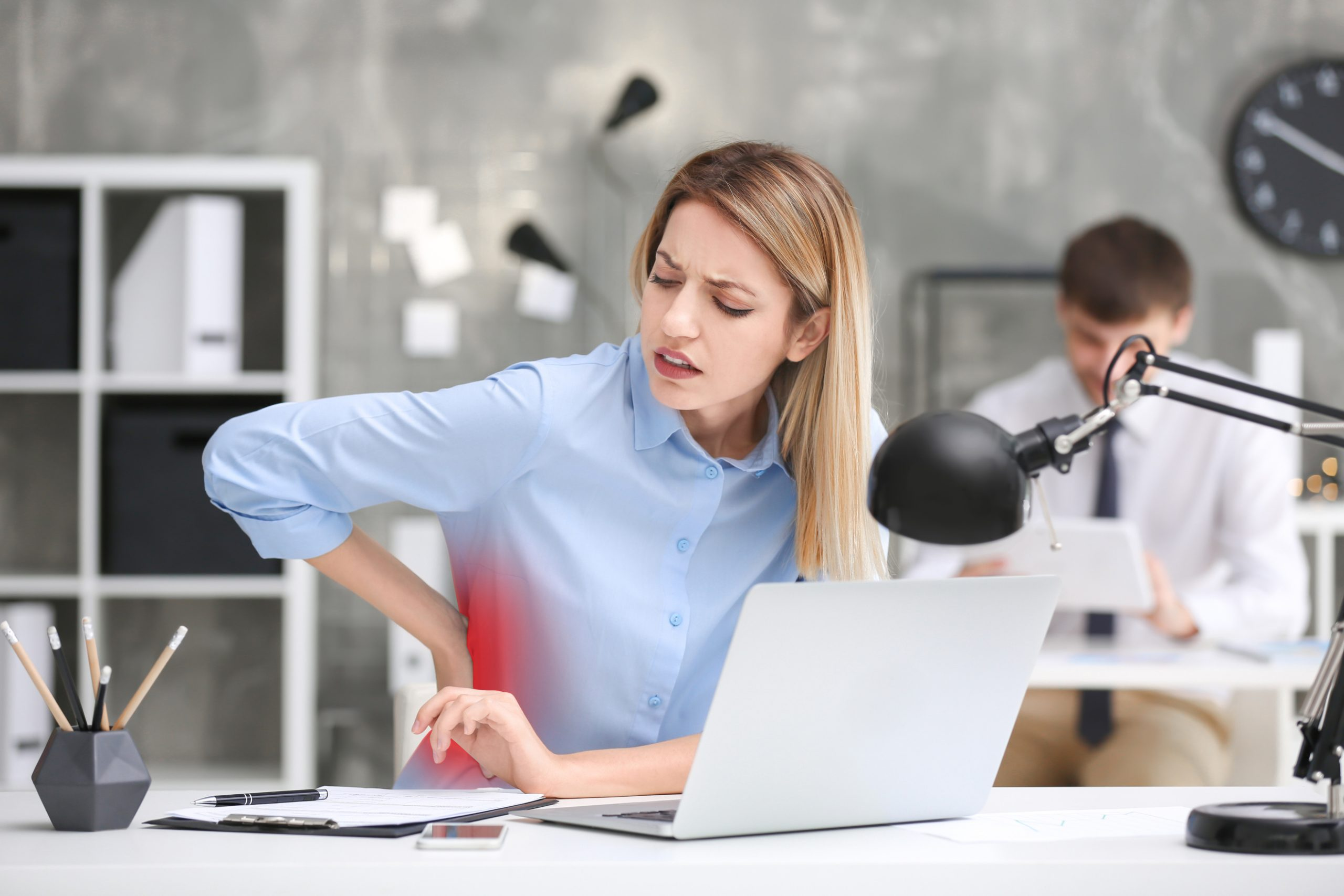 Young woman suffering from back pain at table in office